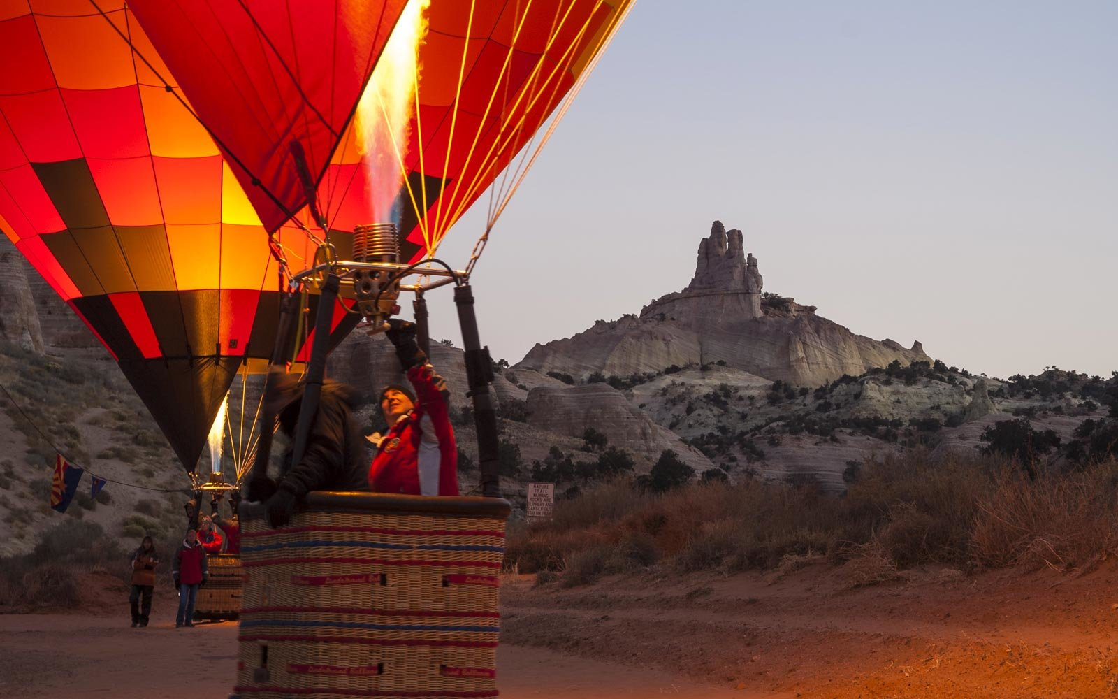 Hot Air balloons at dawn glow with Church Rock in background; 25th Annual Red Rock Balloon Rally at Red Rock State Park, Gallup, New Mexico.