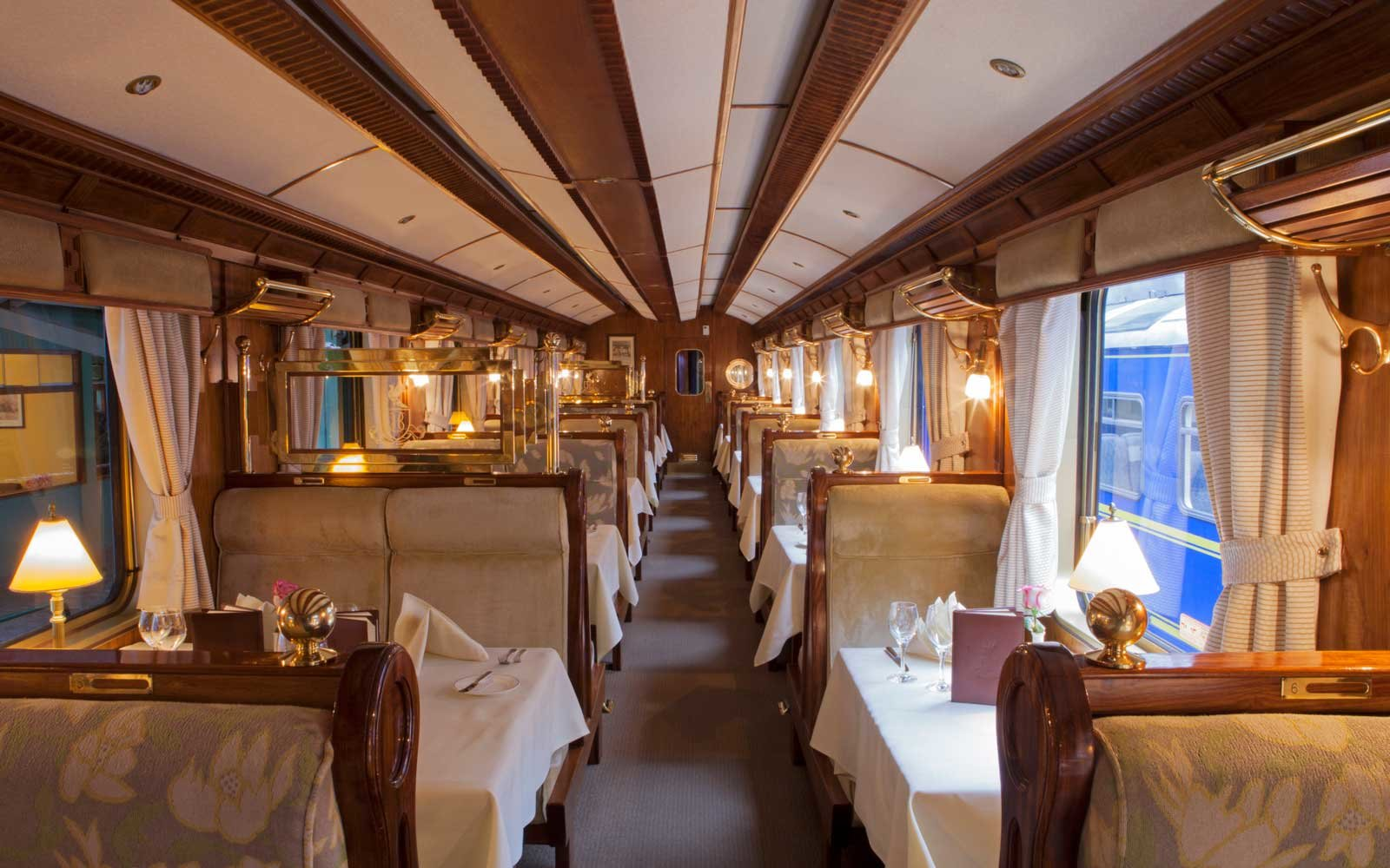 The dining car with tables set for dinner on the Orient-Express Hiram Bingham train which runs between Cusco (Poroy) and Machu Picchu via Ollantaytambo