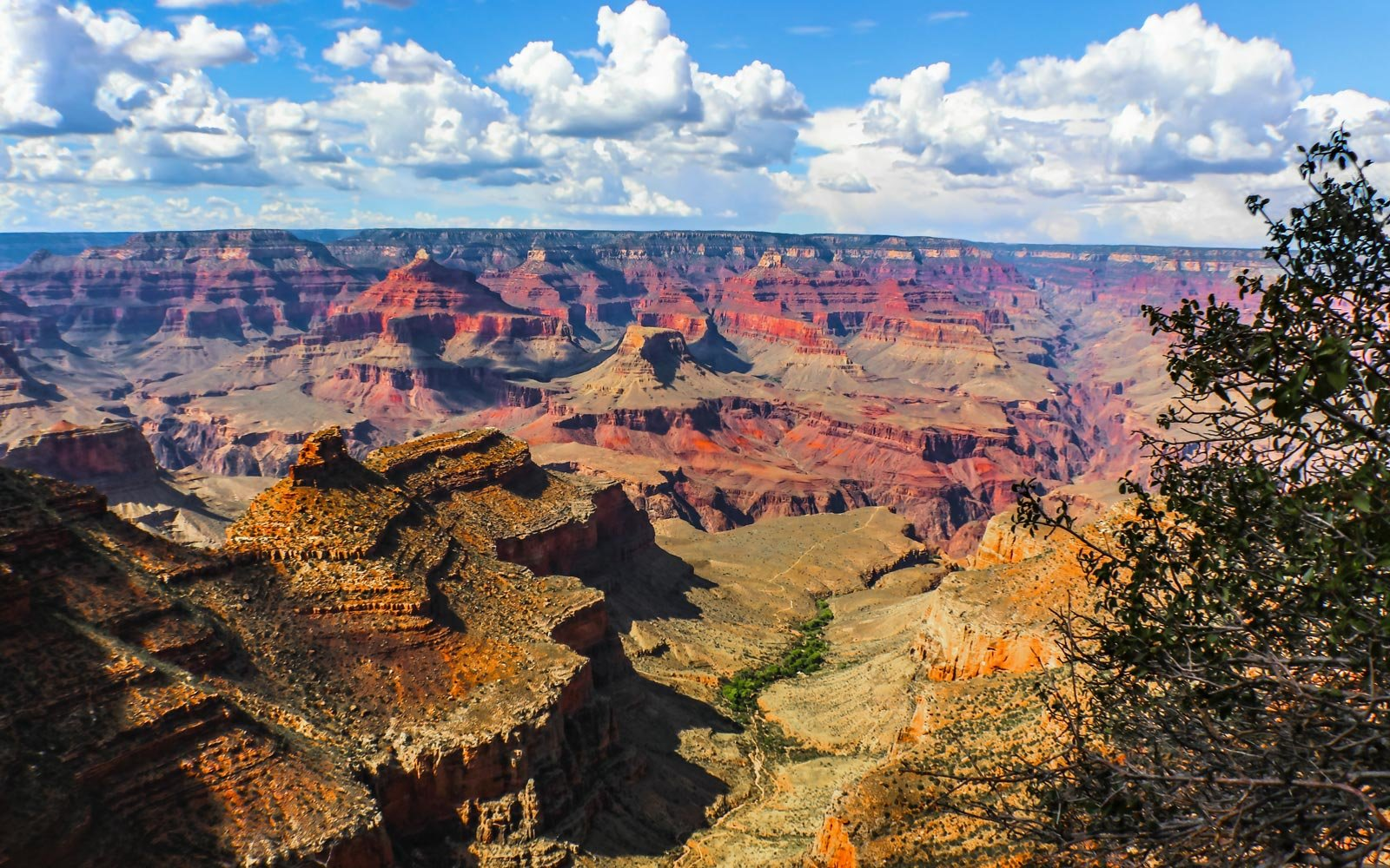 The vastness of the Grand Canyon - View from South Rim at the worlds held in this one majestic canyon with its mesa and rivers and bluffs and cliffs under a dramatic sky