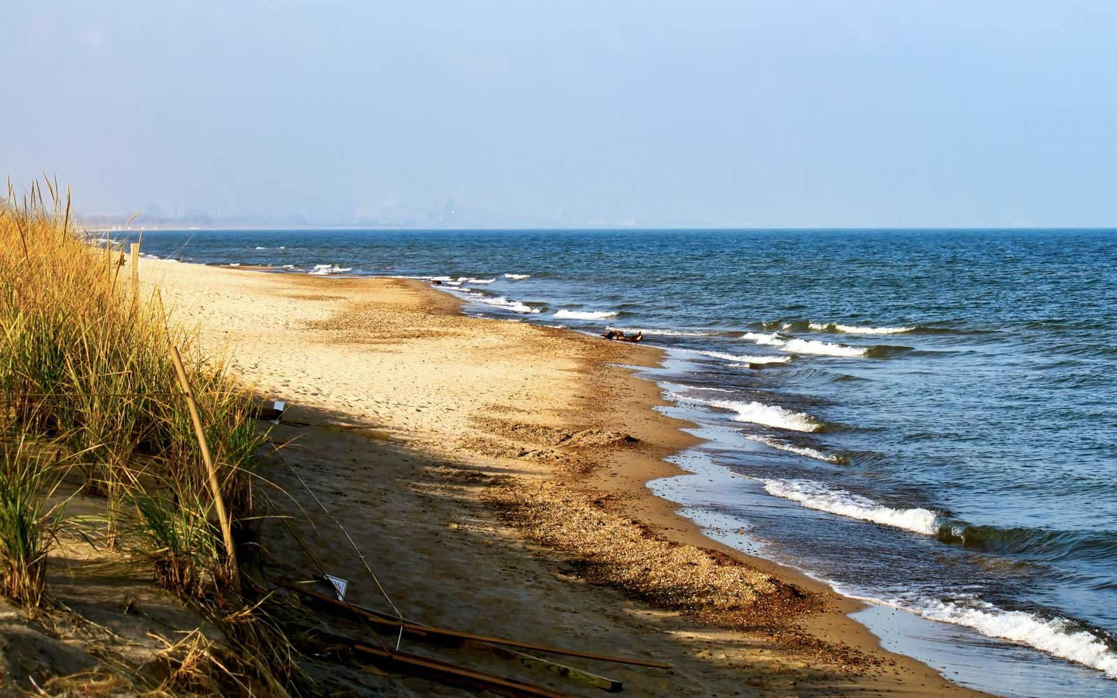 Shoreline of the Indiana Dunes Lakeshore featuring autumn colors and beautiful blue water along sandy beach