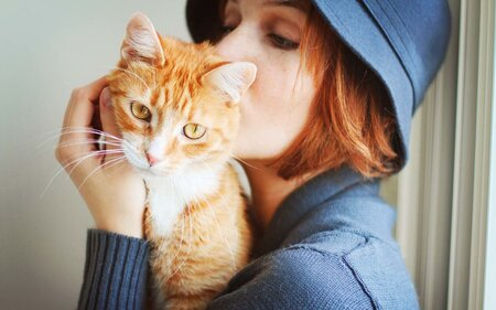 Young Redheaded Girl Holds And Kisses An Orange White Domestic Short Hair Cat