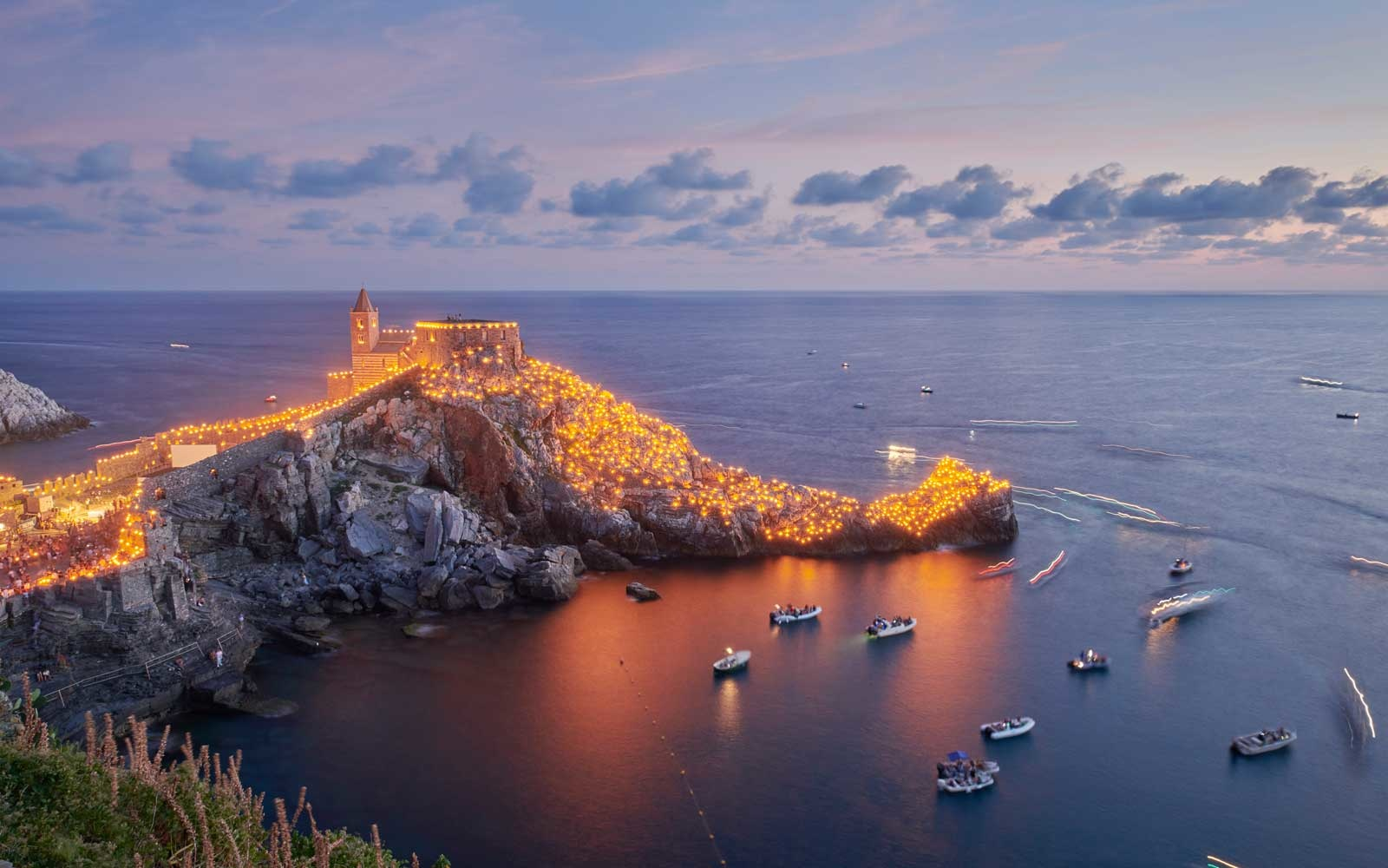 08/17/2019 Porto Venere, Italy. The view on Saint Peter's Church with candles lit all around it, for the celebrations of Madonna Bianca.