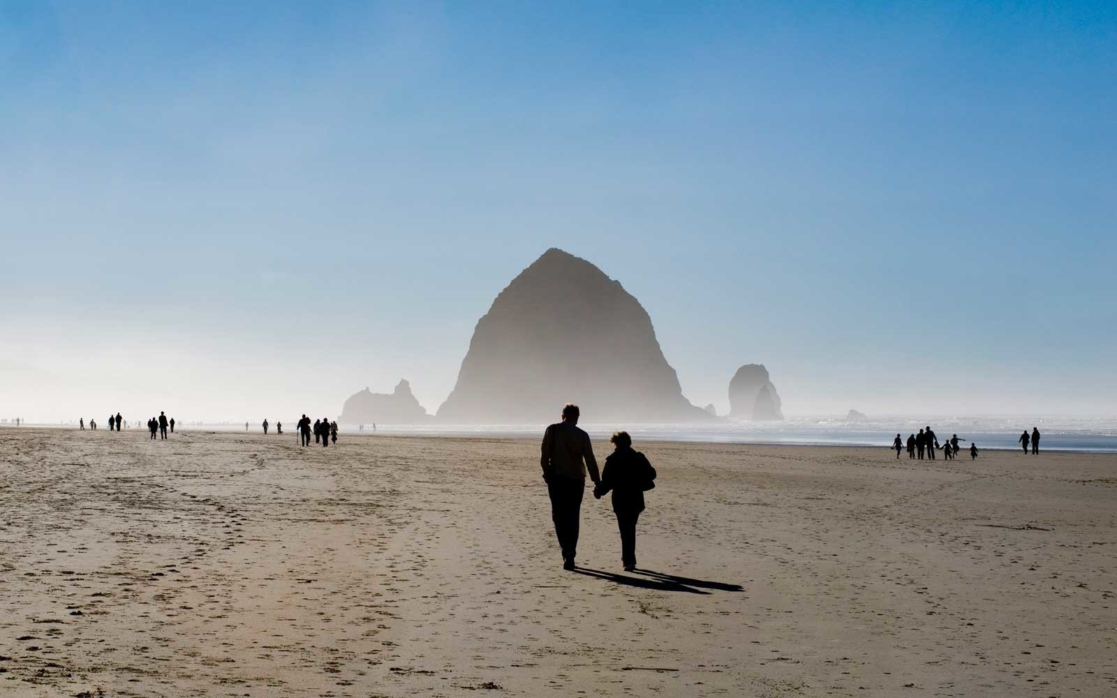 A couple walks hand in hand towards haystack rock on Cannon Beach, OR.