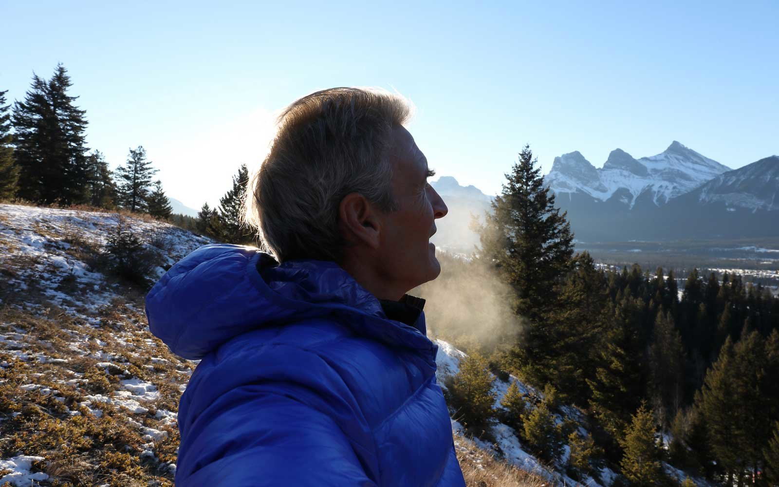Man looks off to distant mountains from hillside on a cold winter day