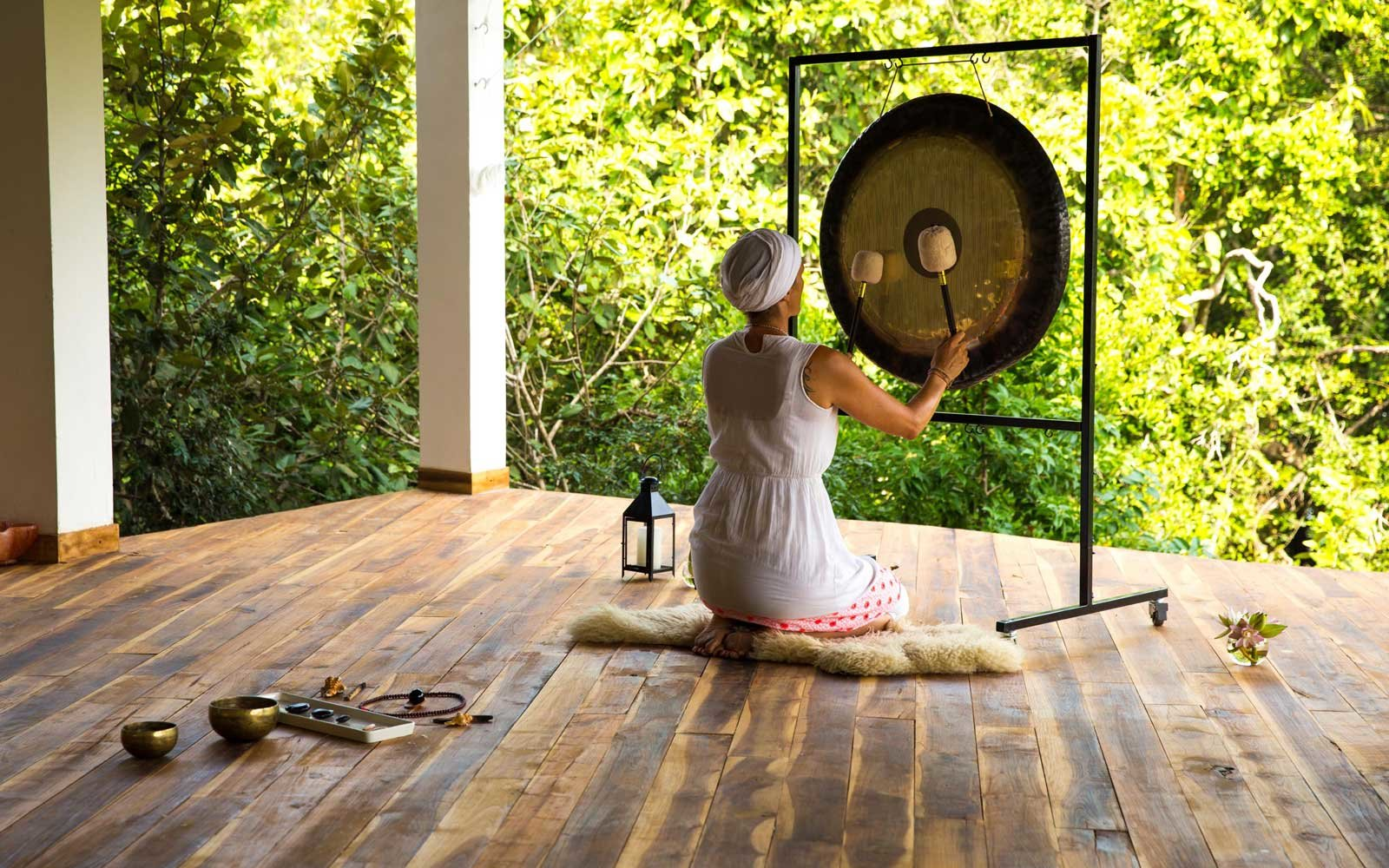 Woman playing a gong at the Sen Wellness retreat in Sri Lanka