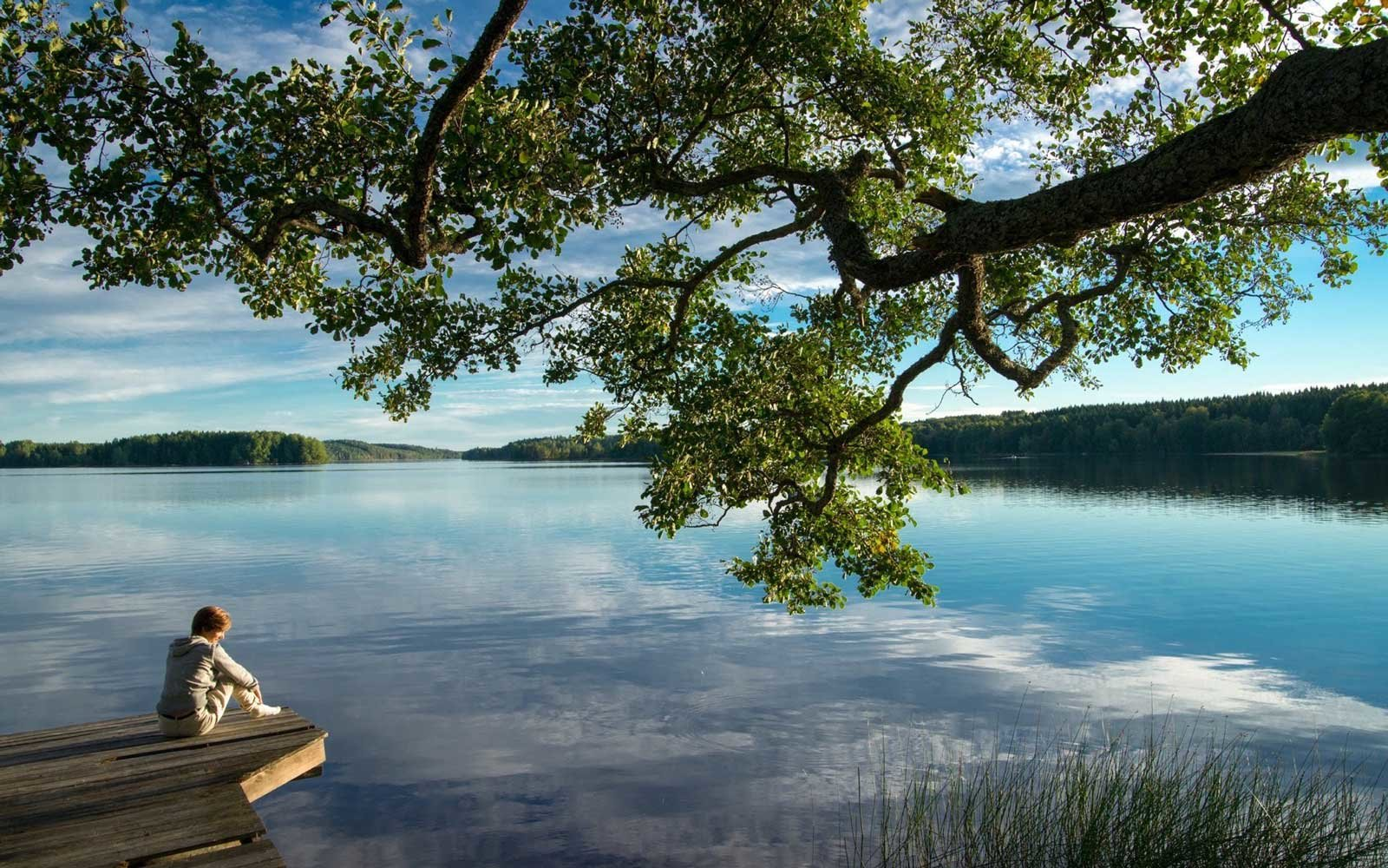 Yoga retreat guest sitting peacefully on a dock beside a lake in Sweden