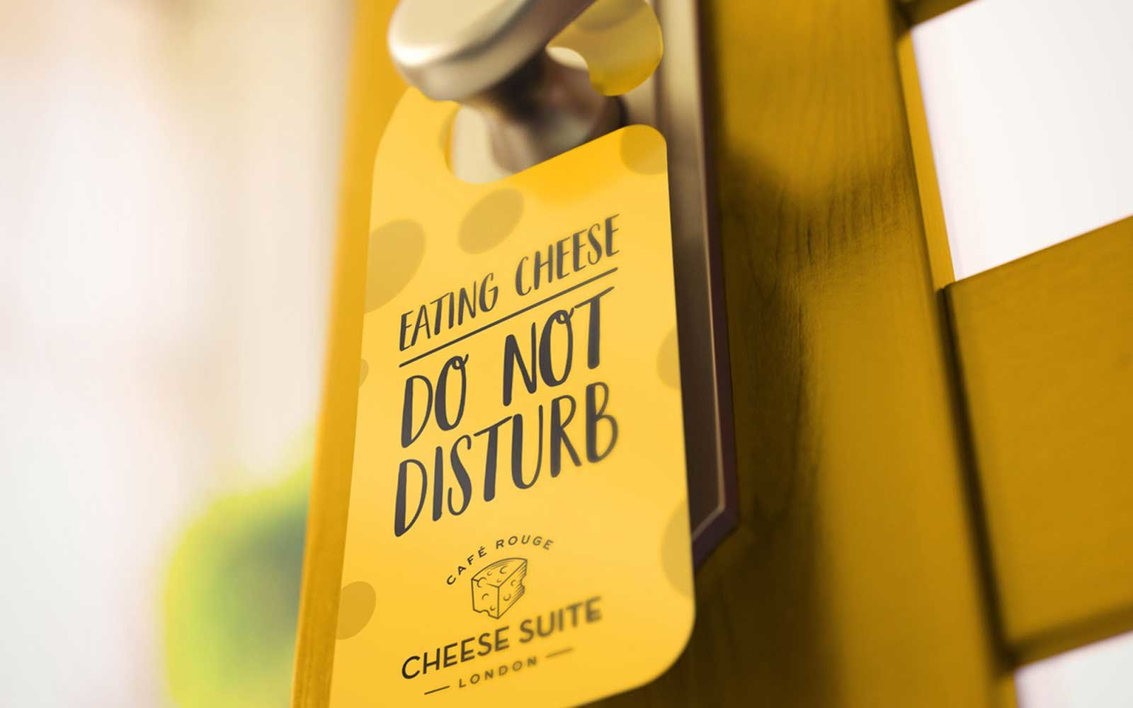 A hotel door hanger that reads 'Eating Cheese, Do not disturb'.