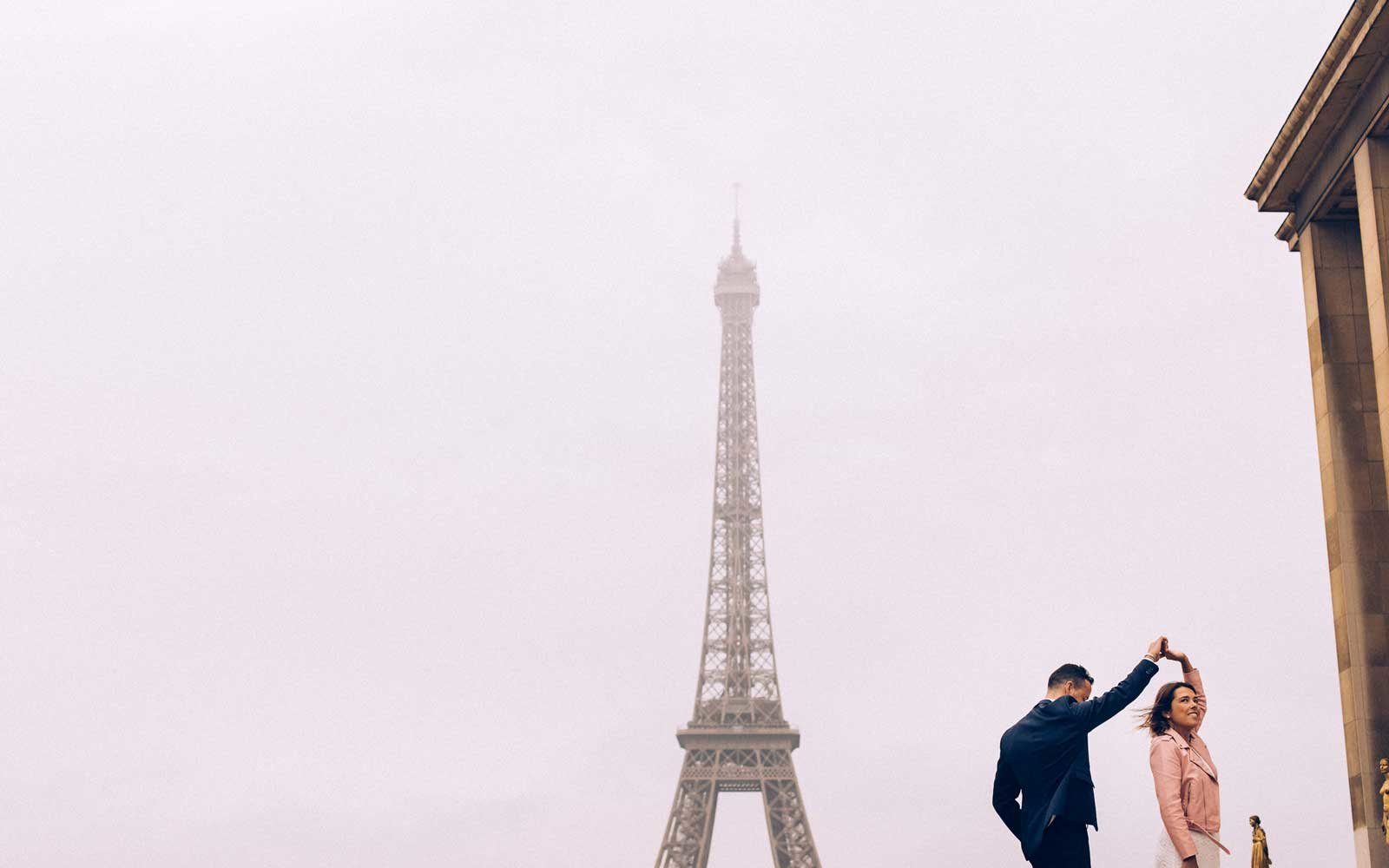 Couple dancing in front of the Eiffel Tower in Paris, France