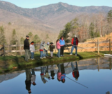 family fishing by pond in Clear Creek Guest Ranch, Burnsville, NC