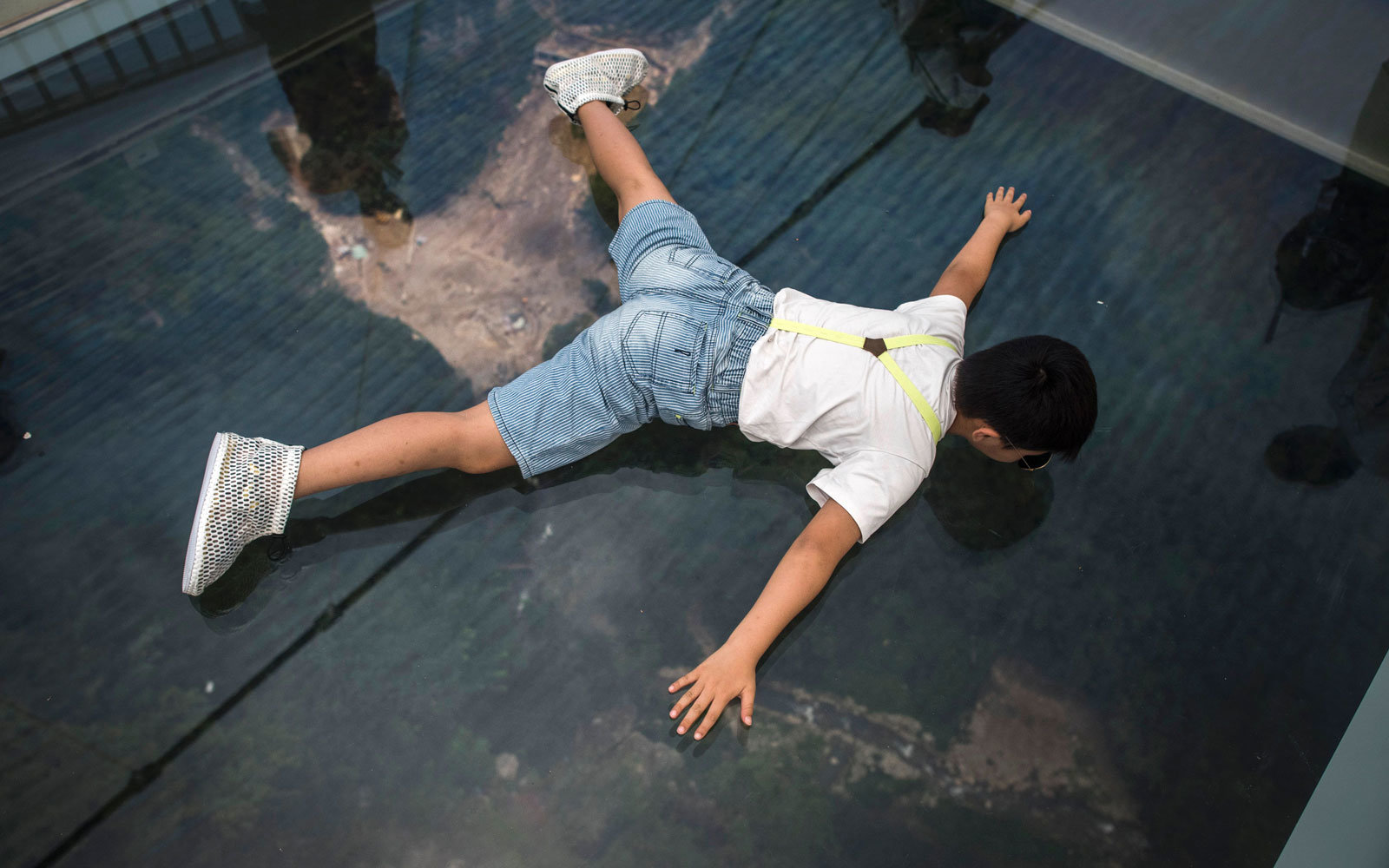 A tourist lays against the glass.