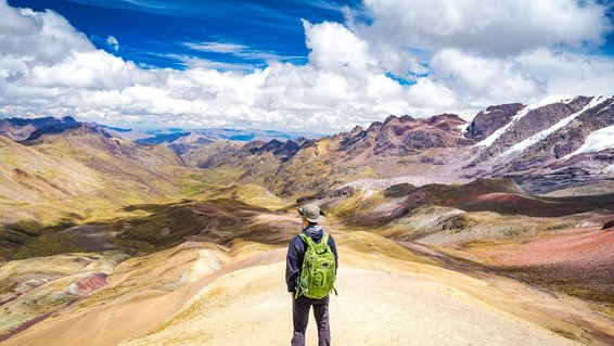 Standing on the top of Rainbow Mountain in Cusco, Peru