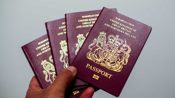 In this photo illustration a man holds 4 British passports
