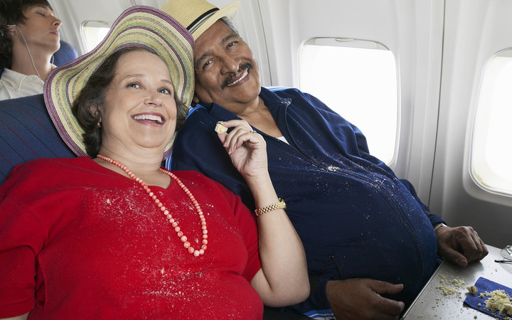 Overweight Senior Couple Sit on a Plane Sharing Cake, Crumbs on Their Clothes