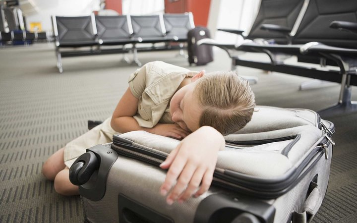 A girl sleeping on a suitcase