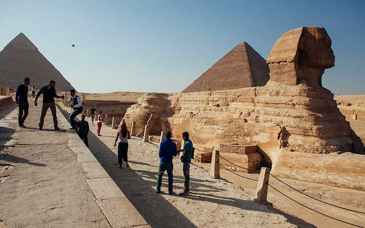 CAIRO, EGYPT - OCTOBER 21: A group of tourists pose for photographs in front of the Sphinx at the Pyramids of Giza compound on October 21, 2013 in Cairo, Egypt. The Pyramids of Giza, one of the seven wonders of the ancient world and built around 2600 B.C.