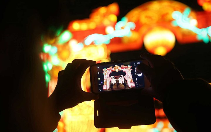 A woman takes a picture with her smartphone of a light corridor during a photocall to promote the Magical Lantern Festival at Chiswick House Gardens in west London on January 18, 2017. 