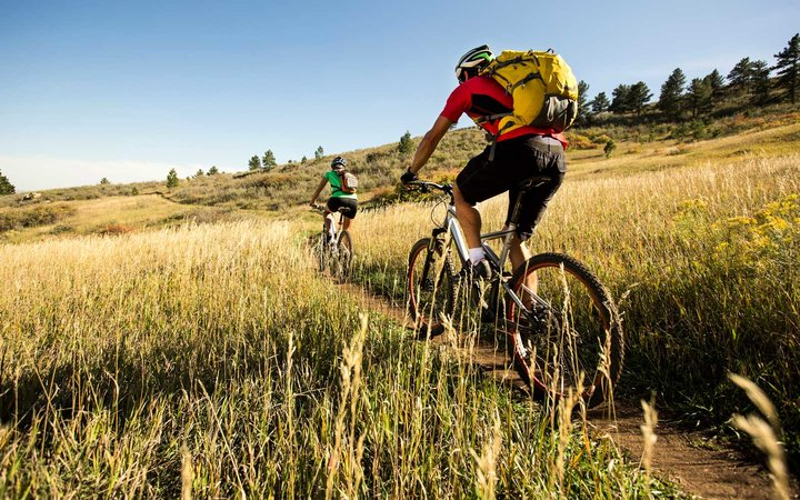 A young couple mountain biking along a double track trail on a sunny day.