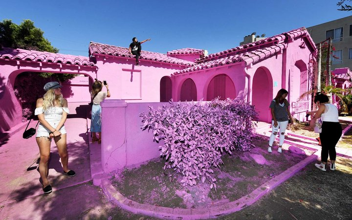 "People pose for photos at the ""Pink Houses"" which have become an pop-up photo opportunity after a local developer hired artist Matty Mo to paint the three houses pink, before there eventual demolition in Los Angeles, California"