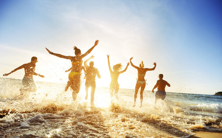 Crowd of people or friends runs to sunset sea. Beach holidays travel concept