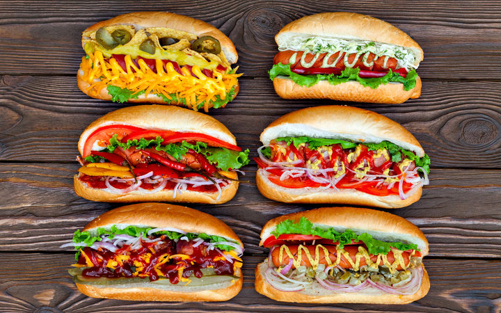 A lot of big delicious hot dogs with sauce and vegetables on wooden background. Their assorted hot dogs to gourmet. View from above.