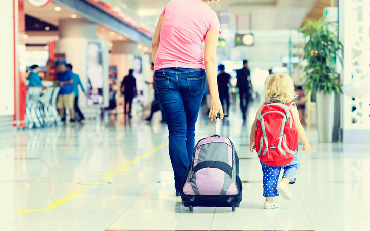 mother and little daughter walking in the airport, family travel