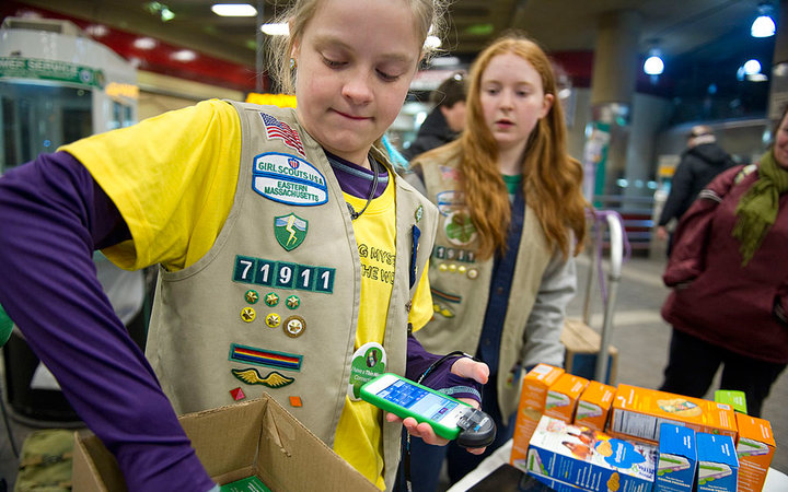 CAMBRIDGE, MASSACHUSETTS - JANUARY 4: Girl Scout Christine MacLeod of Eastern Massachusetts Girl Scout Troop 71911, hands out cookie orders while scanning a credit card on ROAMpay mobile card reader while selling cookies at the Harvard Square subway stop