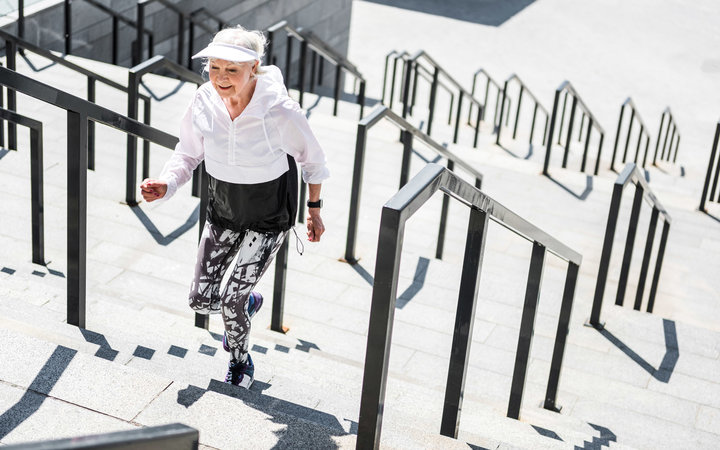 Happy old woman is climbing up city stairs outside. She is smiling and moving ahead. Copy space in right side