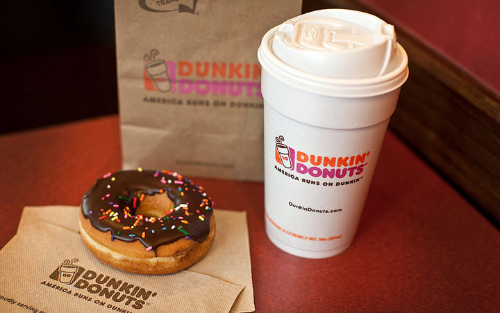 A chocolate glazed donut and a cup of coffee are arranged for a photograph at a Dunkin' Donuts Inc. store in West Orange, New Jersey, U.S., on Thursday, July 7, 2011. Sales at U.S. retailers surpassed analysts' estimates last month as discounts and lower