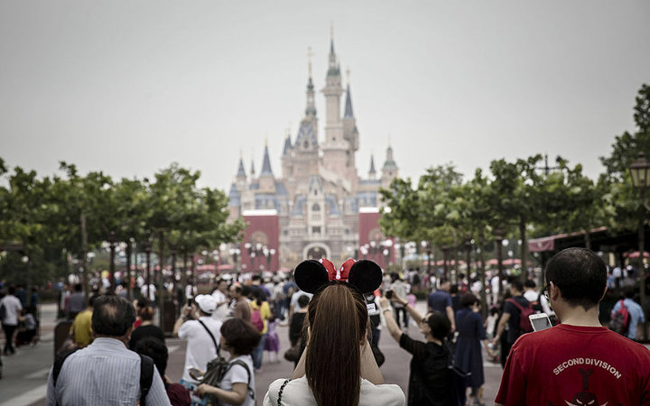 A woman wearing Minnie Mouse ears looks on as the Enchanted Storybook Castle stands at Walt Disney Co.'s Shanghai Disneyland theme park during a trial run ahead of its official opening, in Shanghai, China, on Wednesday, June 8, 2016. With the new $5.5 bil
