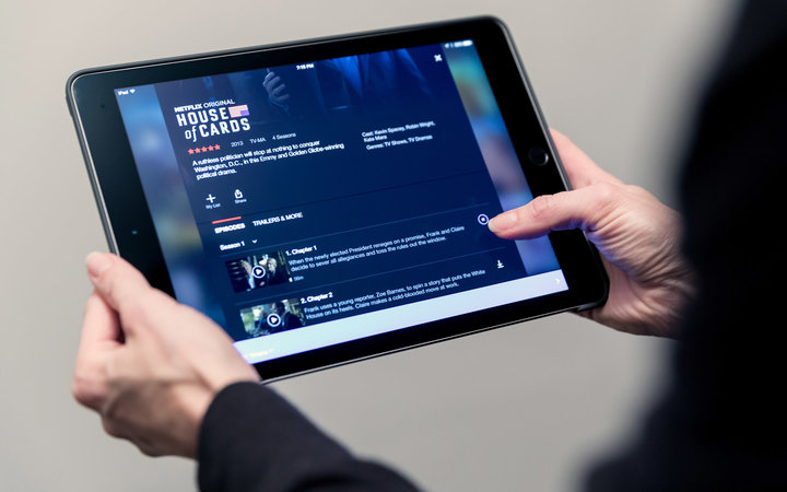 Laval, Canada - November 30, 2016: Human Hand Holding Apple iPad with Netflix Application with the latest download movies and shows option released on November 30th 2016.