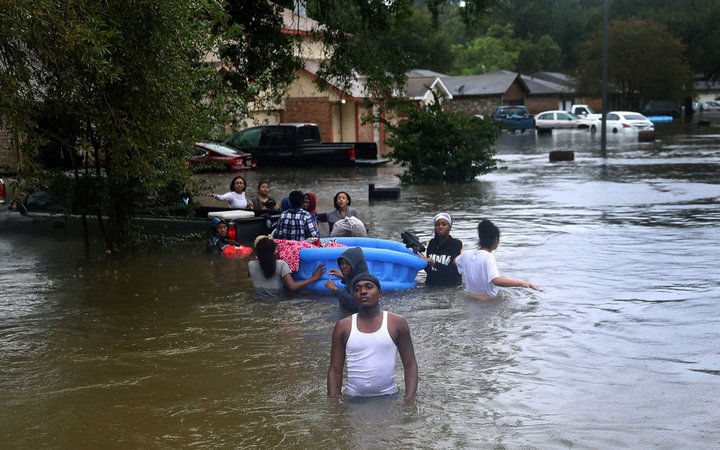 HOUSTON, TX - AUGUST 28:  People walk down a flooded street as they evacuate their homes after the area was inundated with flooding from Hurricane Harvey on August 28, 2017 in Houston, Texas. Harvey, which made landfall north of Corpus Christi late Friday