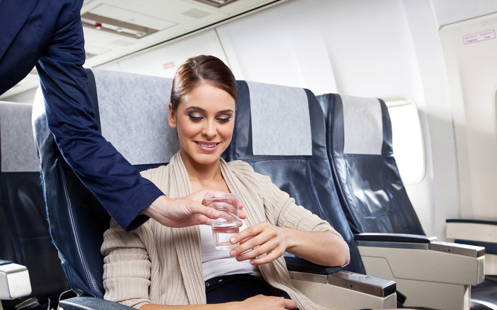 Young woman sitting on the airplane and receiving a glass of water from air stewardess.