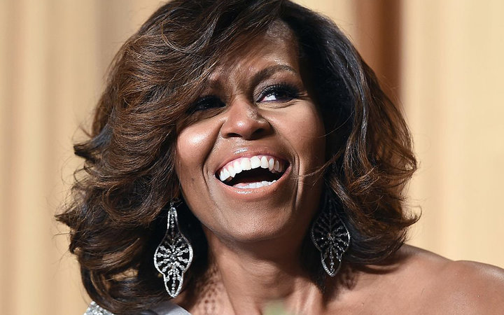 US First Lady Michelle Obama laughs as President Barack Obama tells jokes during the White House Correspondents Association Dinner on May 3, 2014 in Washington, DC. AFP PHOTO/Jewel Samad        (Photo credit should read JEWEL SAMAD/AFP/Getty Images)