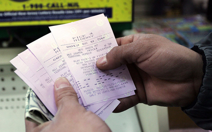 Customer Frank Ruben Acevedo holds a group of 5 Pick 3 and Pick 4 lottery tickets at the Robert Lewis Market Variety store down the street from the New Jersey capitol building in Trenton, New Jersey, on Jan. 24, 2007. Photographer: Emile Wamsteker/Bloombe