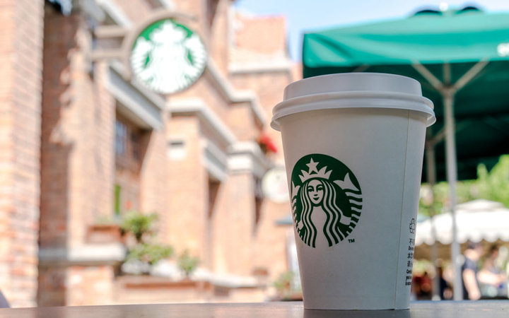 TIANJIN, CHINA - 2017/04/29: Starbucks cup on a roadside table.  According to the report of the second quarter in 2017, the revenue of Starbucks was $5.3 billion, and the sales growth rate of both the global and the United States are 3%, while in China th