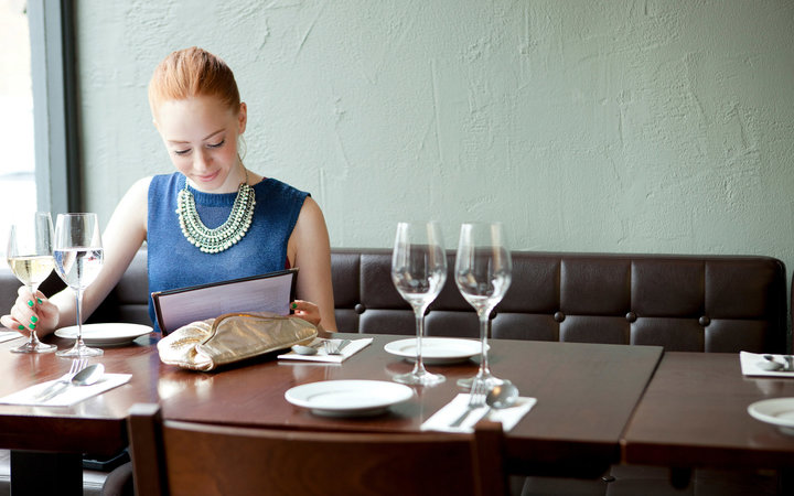 Young woman in restaurant,  reading menu