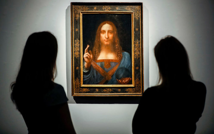 Christie's employees pose in front of a painting entitled Salvator Mundi by Italian polymath Leonardo da Vinci at a photocall at Christie's auction house in central London