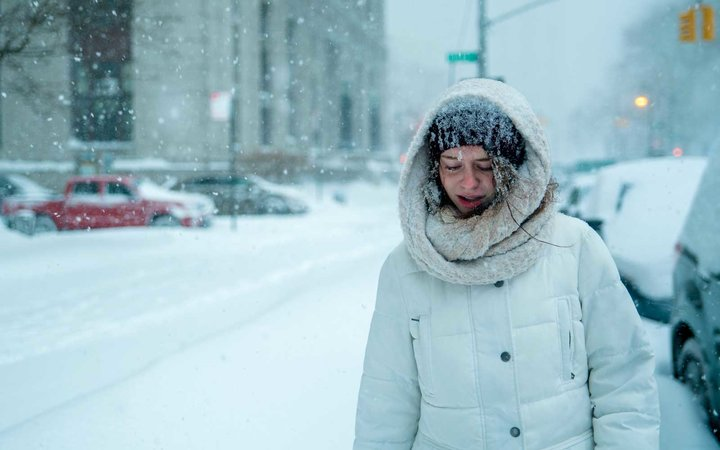 Teenager girl walks under snowfall at the street in Manhattan