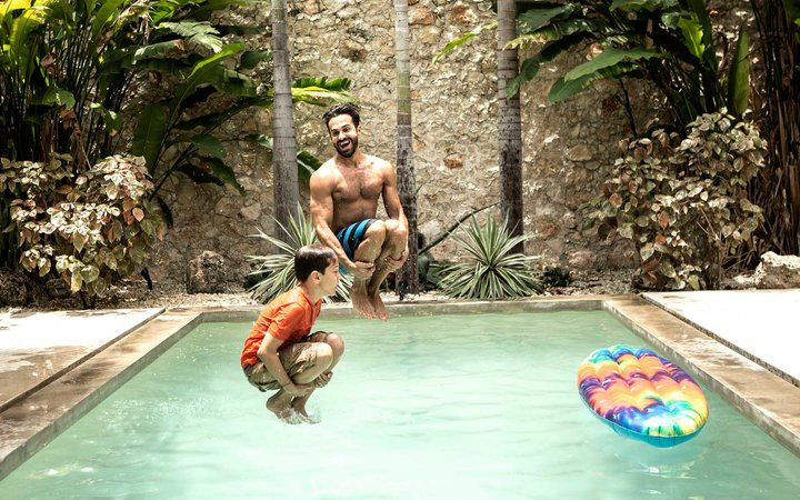 A man and boy in mid air, jumping into a swimming pool