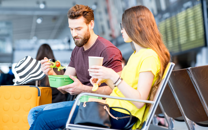 Young couple having a snack with lunch boxes at the waiting hall of the airport during their vacation