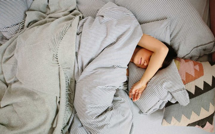 Overhead view of woman lying in bed sleeping