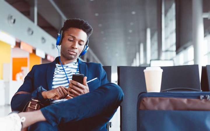 Young man wearing headphones in an airport lounge