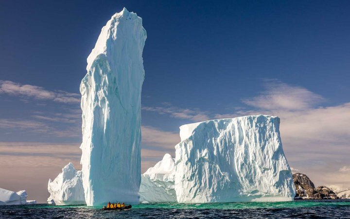 Ice Monolith with group of people in raft, Antarctica