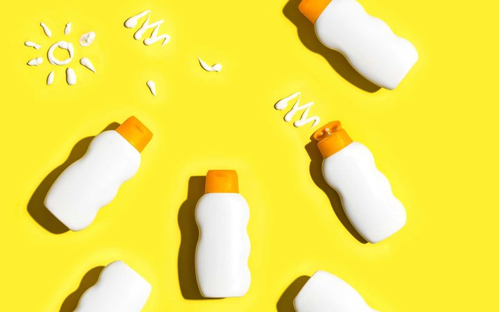 Sunblock bottles a yellow background