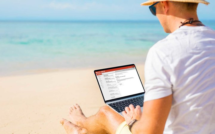 Man working with laptop on the beach.