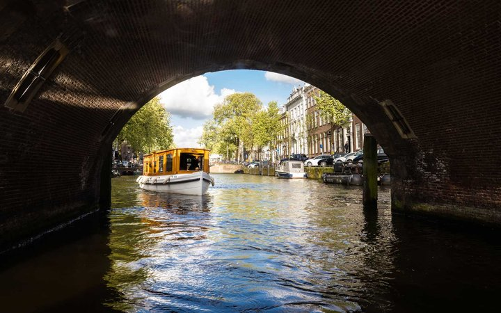 Tourboat about to go under a bridge on Amsterdam canal