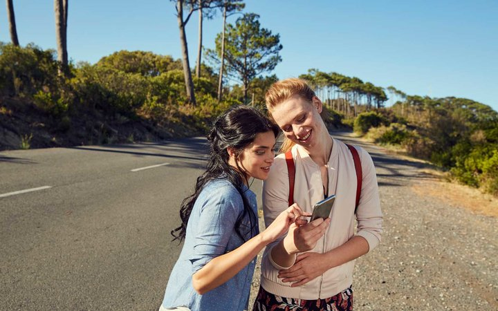 South Africa, Cape Town, Signal Hill, two smiling young women with cell phone on a trip