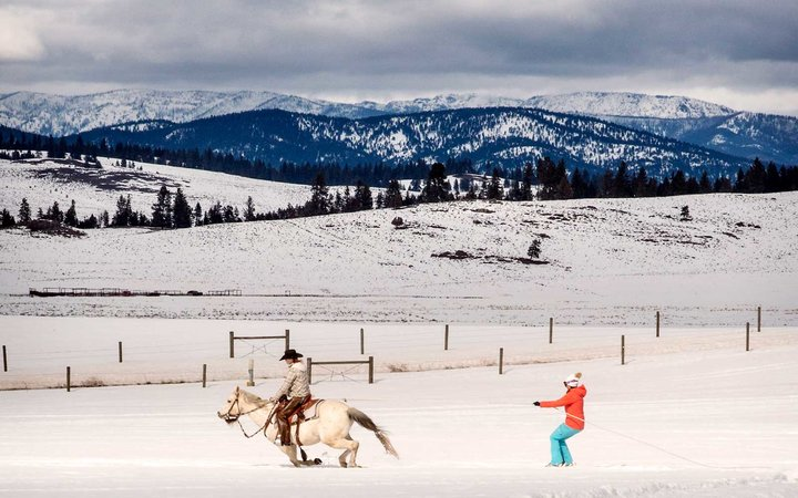 Skijoring (where a skier is pulled behind a horse) at Paws Up luxury guest ranch in Montana