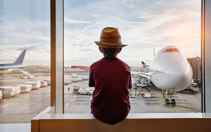 Boy wearing straw hat looking through window to airplane