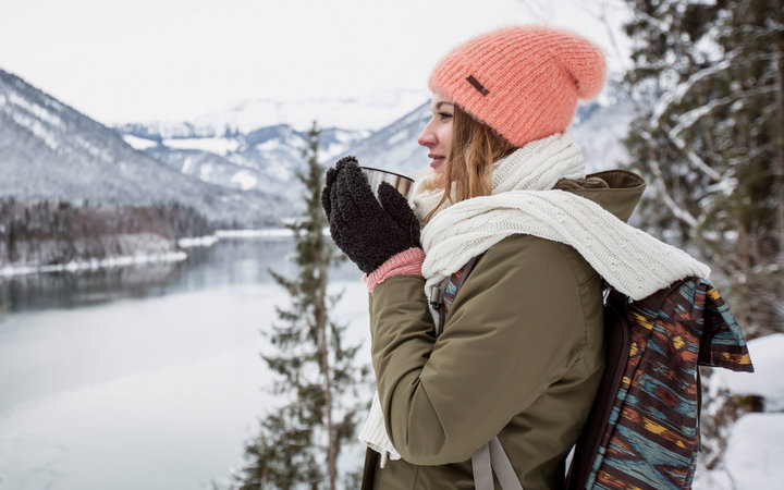 Young woman with hot drink standing in alpine winter landscape with lake